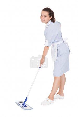 Photo pour Jeune femme de ménage Nettoyage étage avec balai sur fond blanc - image libre de droit