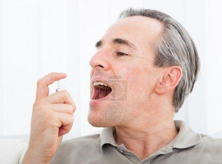 Man applying Fresh breath spray