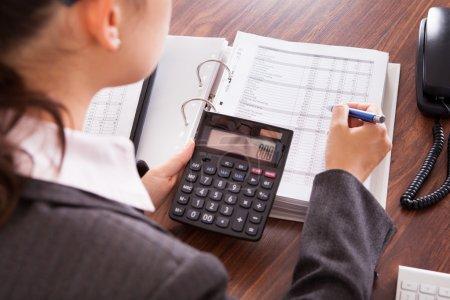 Photo pour Vue épaule de femme d'affaires finances au bureau de calcul - image libre de droit