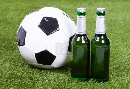 Photo pour Gros plan sur le ballon de football et les bouteilles de bière sur l'herbe verte - image libre de droit