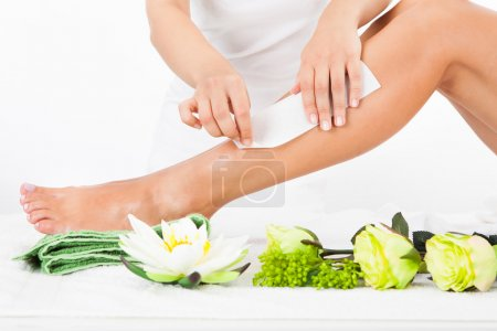 Photo for Beautician Waxing A Woman's Leg In Spa - Royalty Free Image