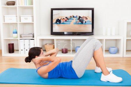 Photo pour Jeune femme faisant de l'exercice sur tapis devant la télévision - image libre de droit