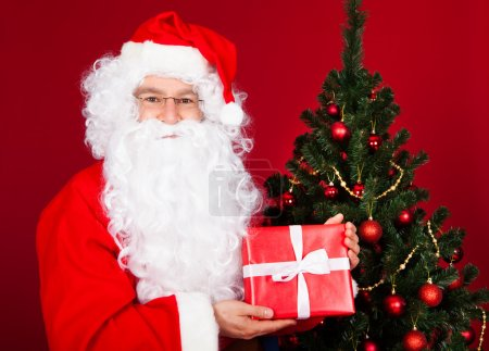 Photo for Portrait of a happy santa holding gift near Christmas tree - Royalty Free Image
