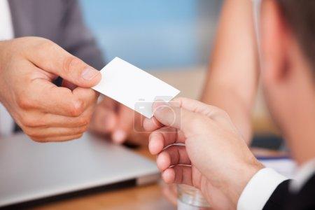 Foto de Primer plano de dos empresarios manteniendo la tarjeta sobre escritorio - Imagen libre de derechos