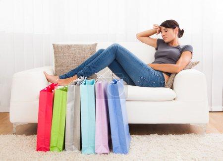 Foto de Mujer cansada sentada en un sofá después de un largo día de compras - Imagen libre de derechos