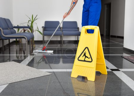 Photo for Close-up Of Man Cleaning The Floor With Yellow Wet Floor Sign - Royalty Free Image