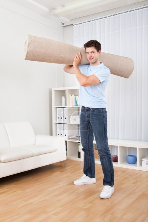 Young Man Holding Carpet