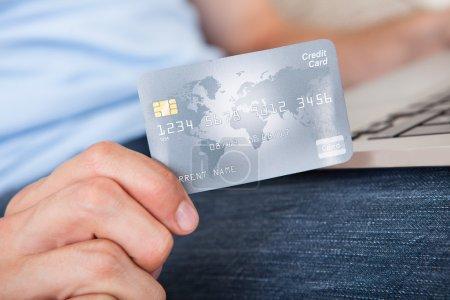 Photo pour Gros plan de l'homme avec l'ordinateur portable et de carte de crédit, achats en ligne - image libre de droit