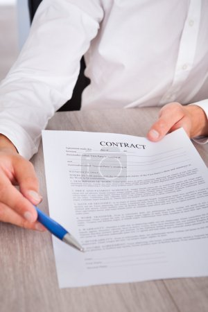 Businessman's Hand Holding Pen And Contract