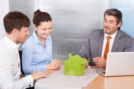 Photo for Happy Young Couple Discussing With Mature Consultant - Royalty Free Image