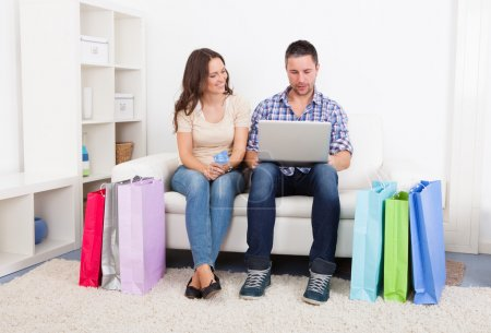 Young Couple Sitting On Couch Shopping Online