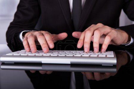 Photo pour Gros plan de la main d'un homme d'affaires de frappe sur le clavier - image libre de droit