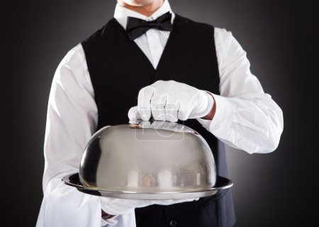 Photo for Portrait Of A Male Waiter Holding Tray And Lid Over Black Background - Royalty Free Image