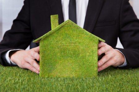 Foto de Primer plano del empresario sosteniendo ecológico casa hecha de hierba - Imagen libre de derechos