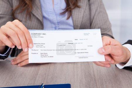 Photo pour Gros plan sur deux hommes d'affaires détenant un chèque au bureau - image libre de droit