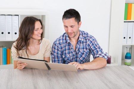Foto de Retrato de la feliz pareja sentada al lado mirando el álbum de fotos - Imagen libre de derechos