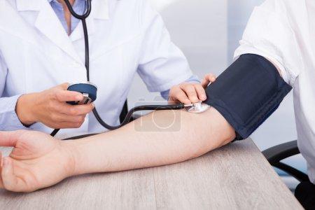 Die Hand des Arztes überprüft den Blutdruck