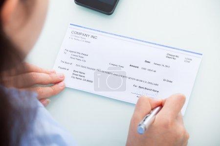 Photo pour Gros plan d'une femme d'affaires remplissant un chèque vierge au bureau - image libre de droit