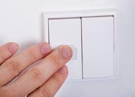Photo pour Gros plan de main appuie sur l'interrupteur sur le mur - image libre de droit