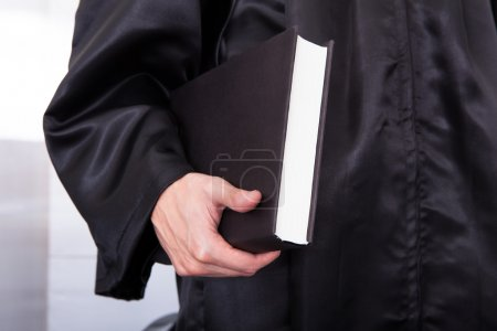 Male Judge Holding Law Book