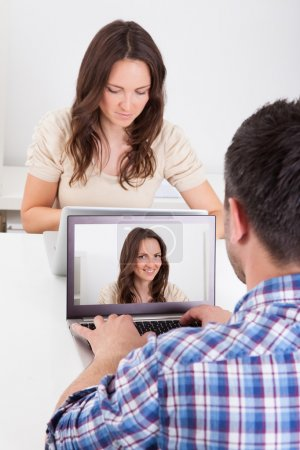 Man Sitting In Front Of Woman Looking At Her Photo