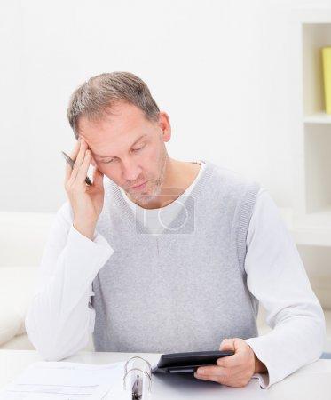 Photo pour Portrait d'un homme réfléchi tenant la calculatrice à la maison - image libre de droit