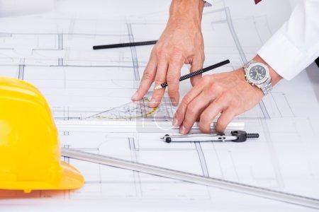 Photo pour Gros plan sur le plan directeur du dessin de l'architecte masculin au bureau - image libre de droit