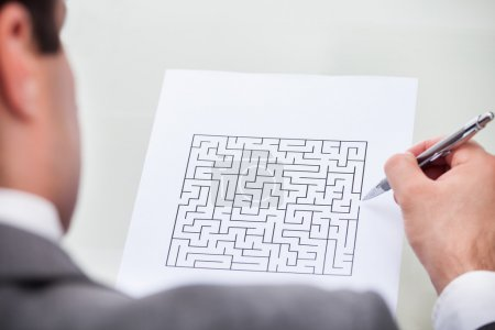 Businessman Looking At Maze Puzzle Holding Pen