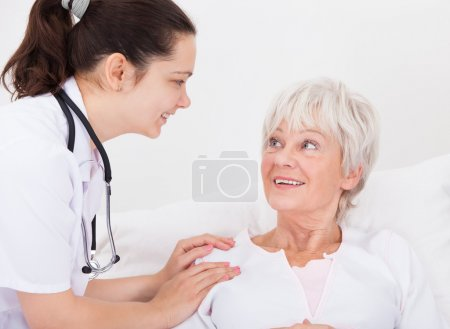 Happy Doctor And Patient Looking At Each Other