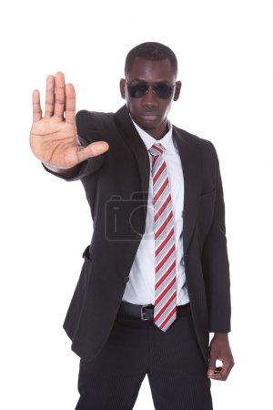 Photo for Portrait Of Young Businessman Wearing Sunglasses Gesturing Stop Sign - Royalty Free Image