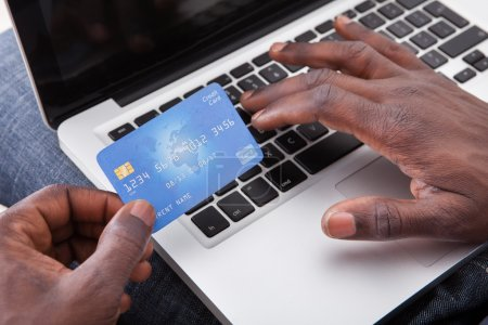 Hand Holding Credit Card With Laptop