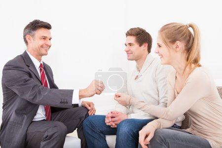 Photo pour Heureux homme consultant donnant carte de visite pour les jeunes couples - image libre de droit