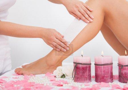 Photo pour Esthéticienne épilation jambe de la femme, appliquer la bande de cire - image libre de droit