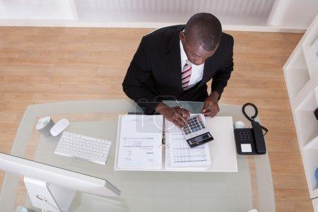 Photo pour Jeune homme d'affaires africain, calcul des projets de loi de finances avec calculatrice - image libre de droit