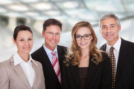Photo pour Groupe souriant de professionnels d'affaires élégants debout dans une rangée avec les bras croisés regardant la caméra - image libre de droit