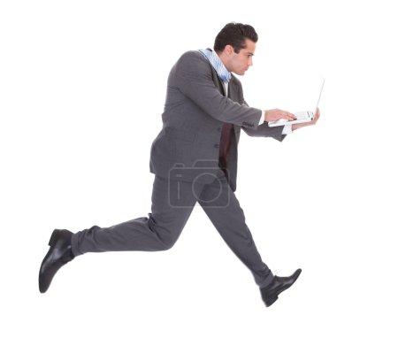 Businessman Using Laptop While Running