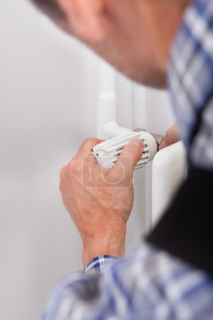Plumber Fixing Thermostat