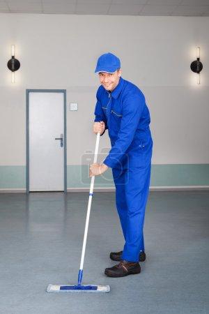 Photo pour Heureux mature mâle travailleur nettoyage sol avec balai - image libre de droit