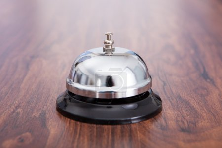 Photo for Close-up Of Hand Ringing Service Bell Kept On Wooden Table - Royalty Free Image