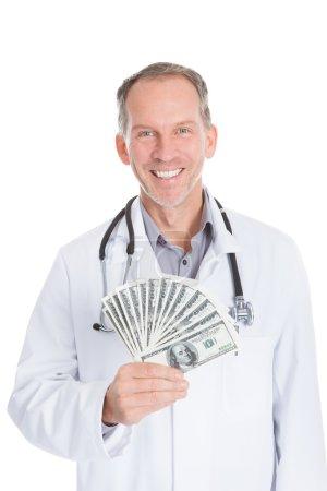 Photo pour Portrait de l'heureux homme mature médecin détenant des billets de banque - image libre de droit