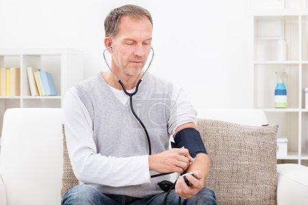 Photo pour L'homme assis sur le canapé vérifiant sa propre pression artérielle - image libre de droit