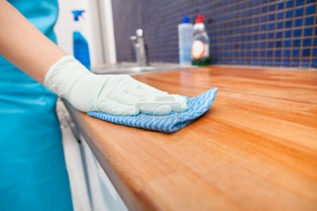Photo for Closeup Of Young Woman Wearing Apron Cleaning Kitchen Worktop - Royalty Free Image