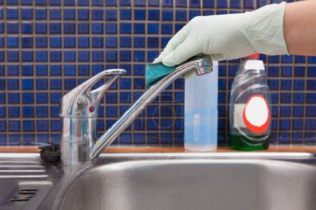 Woman Cleaning Kitchen Faucet