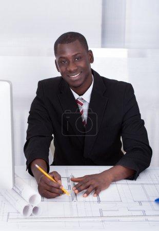 Photo for Happy Young Male African Architect Drawing Blueprint - Royalty Free Image