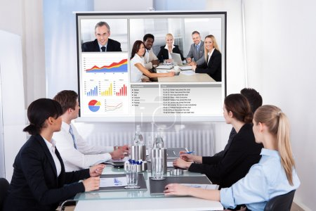 Photo for Businesspeople Sitting In A Conference Room Looking At Screen - Royalty Free Image