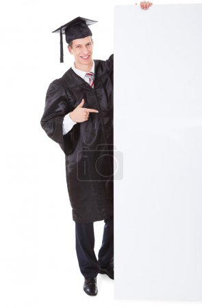 Photo for Young Graduate Man Holding White Billboard Over White Background - Royalty Free Image