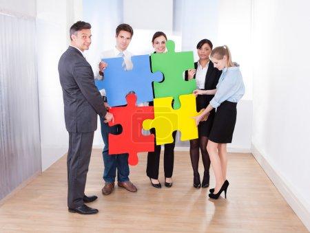 Photo pour Vue à angle élevé des hommes d'affaires tenant puzzle multicolore - image libre de droit