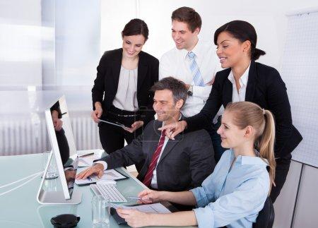 Photo pour Portrait de gens d'affaires heureux en regardant d'ordinateur de bureau - image libre de droit
