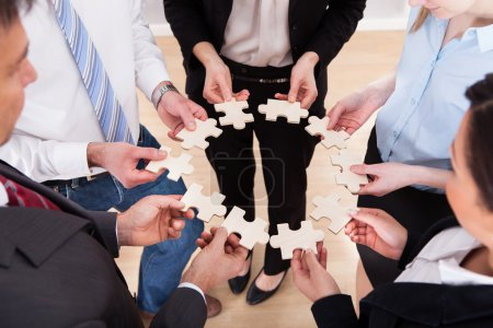 Photo for High Angle View Of Business People Assembling Jigsaw Puzzle - Royalty Free Image