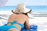 Mladá žena v klobouku proti slunci seběhla relaxaci na pláži